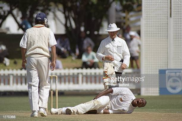 Dave Lawrence of England lies in agony after breaking his kneecap during the Third Test match against New Zealand at the Basin Reserve in Wellington...