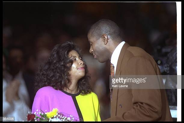 Guard Earvin Johnson of the Los Angeles Lakers kisses his wife Cookie at his retirement ceremony Mandatory Credit Ken Levine /Allsport Mandatory...