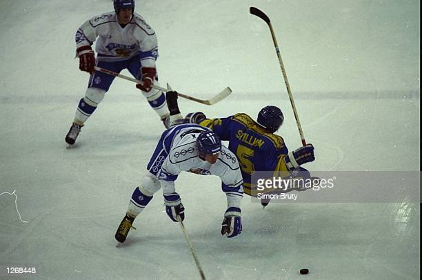 Makela of Finland tackles Stillman of Sweden during the match at the 1992 Winter Olympic Games in Albertville France The match ended in a 22 draw...