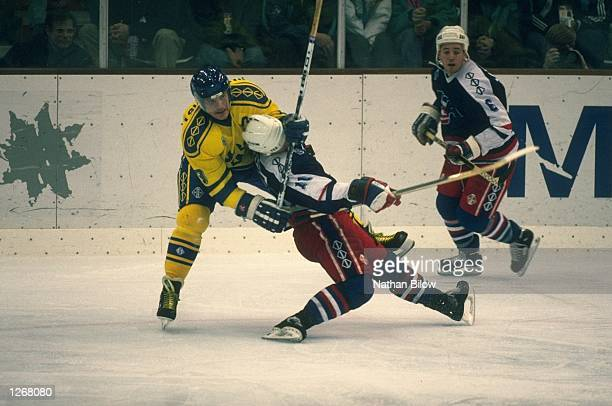 Steve Heinze of the USA is tackled by a Swedish player during the Ice Hockey match at the 1992 Olympic Games in Albertville France Mandatory Credit...