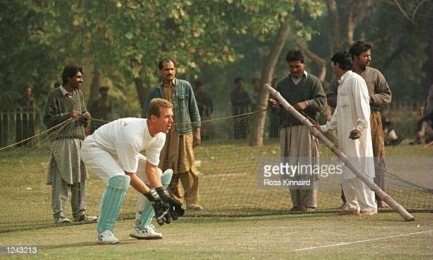 Alec Stewart of England in action as the local groundsmen construct the nets during the training session at the Bagh-e-Jinnah cricket ground in...