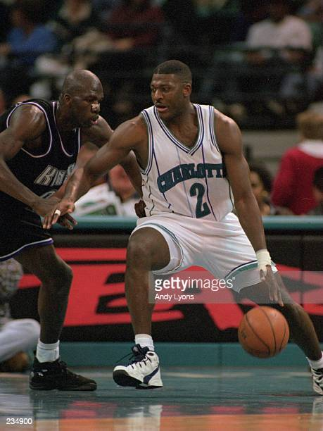 Forward Larry Johnson of the Charlotte Hornets attempts to dribble drive around a defender from the Sacramento Kings during the Hornet''s 115105...