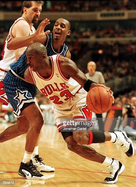 Forward Michael Jordan of the Chicago Bulls drives around a pick set by teammate Bill Wennington on forward Anfernee ''Penny'' Hardaway of the...