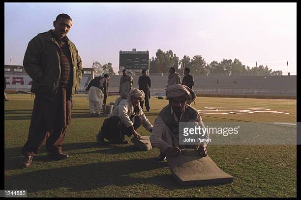 Groundstaff mop up the pitch during a cricket world cup match in Rawalpindi, Pakistan.