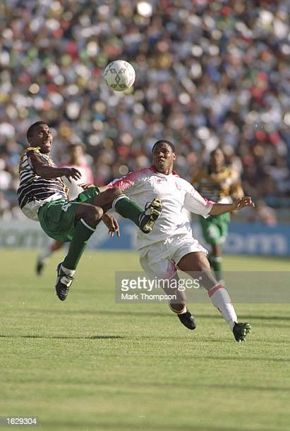 Lucas Radebe of South Africa leaps in the air to challenge Slimane Medhi of Tunisia during the Cup of African Nations Final in Johannesburg South...