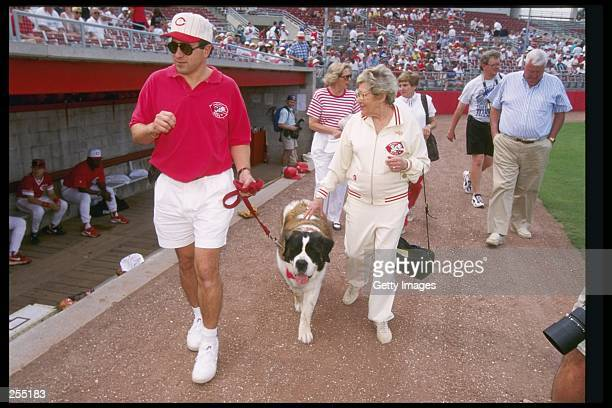 Cincinnati Reds owner Marge Schott walking past the Cincinnati Reds dugout with her dog Schottzie during a spring training game against the Texas...