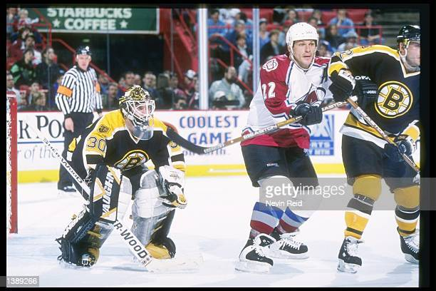 Goaltender Bill Ranford watches defenseman Don Sweeney of the Boston Bruins and right wing Claude Lemieux of the Colorado Avalanche fight for...