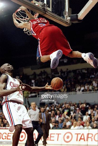 Guard Allen Iverson of the Philadelphia 76ers hangs on the basket rim as Los Angeles Clippers guard Malik Sealy goes for the ball during a game at...