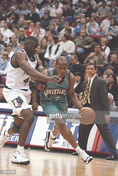 Guard Anthony Peeler of the Vancouver Grizzlies drives the ball past guard Chris Carr of the Minnesota Timberwolves during a game at the Target...