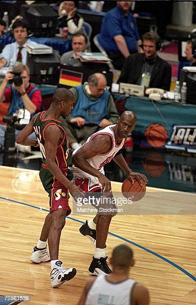 Michael Jordan of the Chicago Bulls dribbles on the court as Gary Payton of the Seattle SuperSonics guards him during the NBA AllStar Game at the...