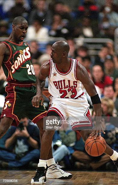 Michael Jordan of the Chicago Bulls dribbles the ball as he is guarded by Gary Payton of Seattle SuperSonics during the NBA AllStar Game at the Gund...