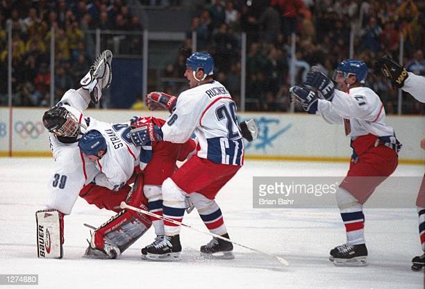 Domink Hasek of the Czech Republic is toppled by teammates Martin Straka and Martin Rucinsky after they beat Canada in an overtime shootout at Big...