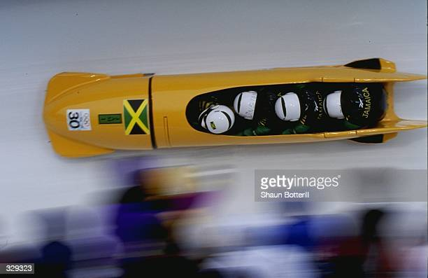Dudley Stokes,Winston Watt,Nelson Stokes and Wayne Thomas of Jamaica compete in the four man bobsled competition at the Spiral during the 1998 Winter...
