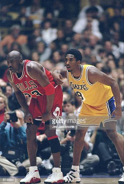 Guard Michael Jordan of the Chicago Bulls and guard Kobe Bryant of the Los Angeles Lakers look on during a game at the Great Western Forum in...