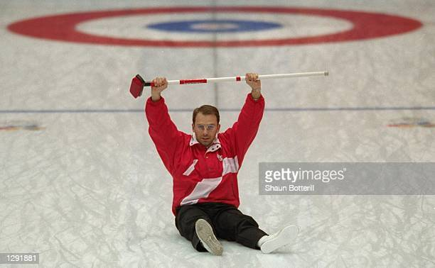 Patrick Huerliman of Switzerland raises his arms in victory after they won the gold medal in the mens curling at Kazakoshi Park Arena during the 1998...