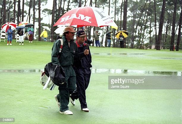 Tom Watson walks under an umbrella with his caddie during the ATT National ProAm at Poppy Hills Golf Course in Pebble Beach California Mandatory...
