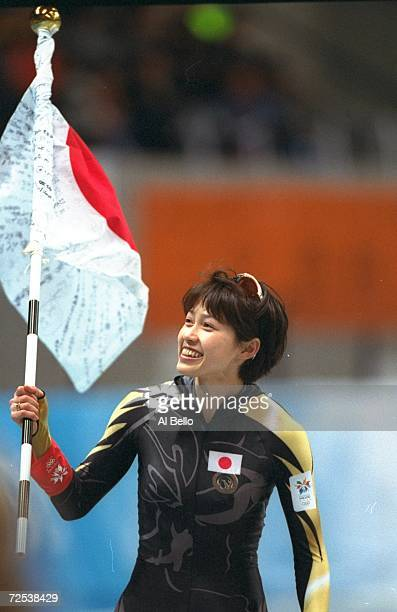Tomomi Okazaki of Japan waves the flag during the womens 500m speed skating competition at the M-Wave Arena during the 1998 Winter Olympic Games in...