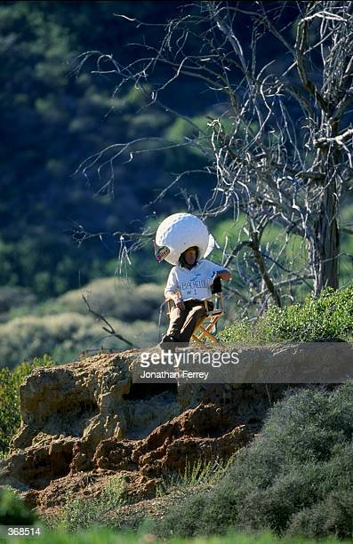 A fan wearing a golf ball hat and a sign which reads ' Bachelor' perches his chair on a cliff to watch the players during the Buick Inviational at...