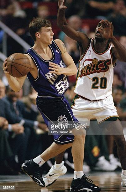 Jason Williams of the Sacramento Kings passes the ball as he is blocked by Gary Payton of the Seattle SuperSonics at the Key Arena in Seattle...