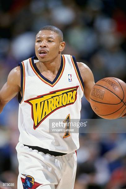 Tyrone Bogues of the Golden State Warriors dribbles the ball during the game against the Seattle Supersonics at the Oakland Coliseum Arena in Oakland...