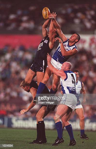 Adam Lange#27 for the Kangaroos and a Carlton opponent fly over the pack as Lance Whitnall#8 of Carlton and Mick Martyn for the kangaroos attempt to...