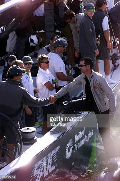 Paul Cayard of AmericaOne shakes the hand of Francesco de Angelis of Prada after Prada won the Louis Vuitton Cup after beating AmericaOne in the last...