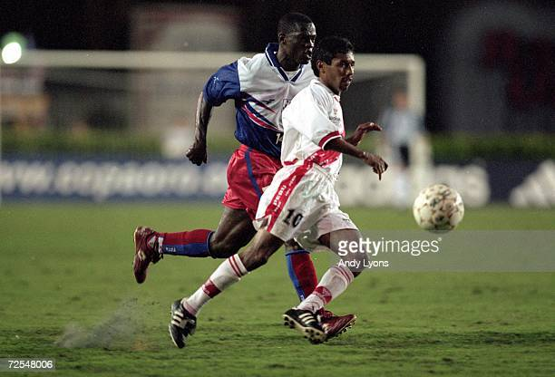 Roberto Palacios of Peru runs with the ball as Wilfred Montilas of Haiti runs next to him during the Gold Cup 2000 Game at the Orange Bowl in Miami...