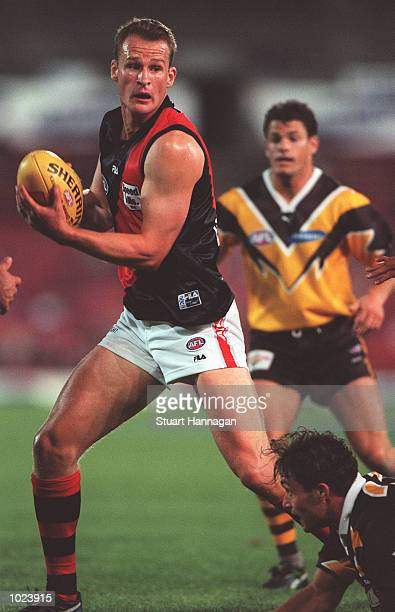 Sean Wellman for Essendon looks to give off the hand pass in the match between Hawthorn and Essendon during round three of the AFL Ansett Cup played...