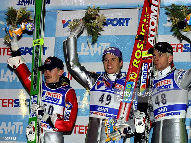 Adam Malysz in second place, Martin Schmitt in first place and Janne Haonen in third place celebrate their placings on the podium during the Ski...
