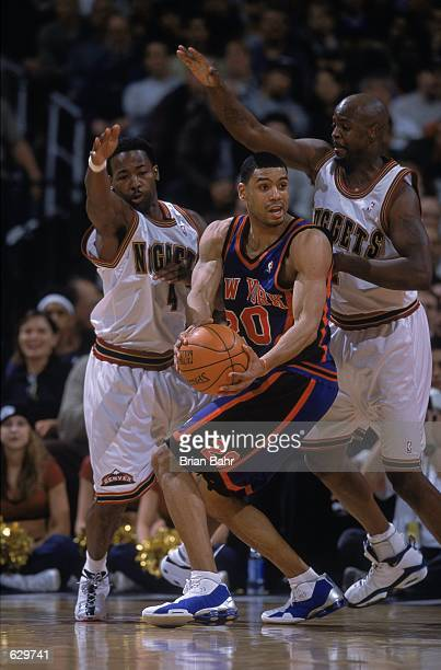Allan Houston of the New York Knicks moves to hand off the ball as he is guarded by George McCloud and Anthony Goldwire of the Denver Nuggets at the...