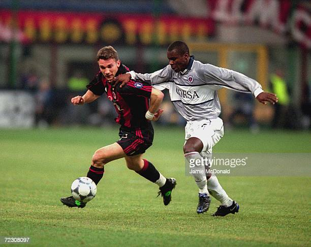 Andrei Shevchenko of AC Milan takes the ball past Aliou Cisse of Paris St Germain during the UEFA Champions League Group B match played at the San...