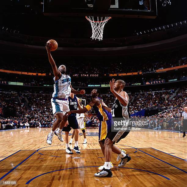 Baron Davis of the Charlotte Hornets drives to the basket against Kobe Bryant and Tim Duncan during the 2002 NBA All Star Game at the First Union...