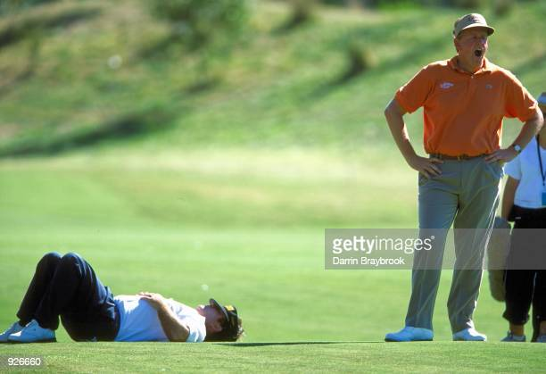 Colin Montgomerie of Scotland takes a break with Craig Parry of Australia as the heat takes its toll on the 17th hole during the final round of the...
