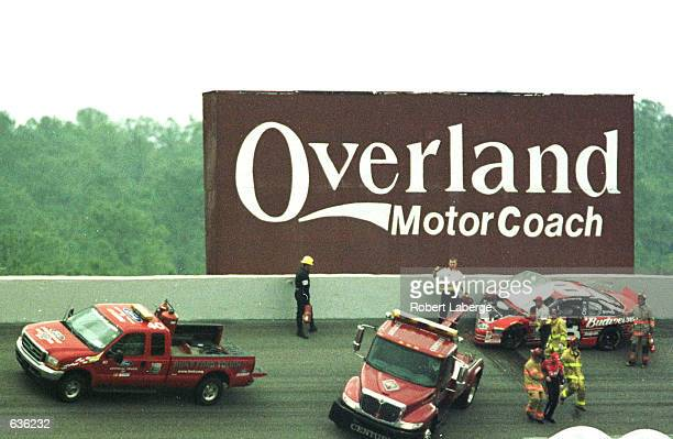 Dale Earnhardt Jr is helped away from his wrecked car after a first lap accident during the NASCAR Winston Cup DuraLube 400 at the North Carolina...