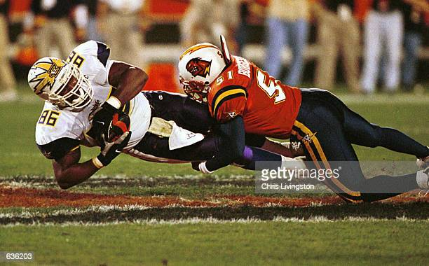 Ed Smith of the Birmingham Bolts is pulled down by Orlando Rage linebacker James Burgess following a first half reception during a first half...