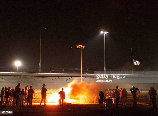Fans hold a bonfire vigil by the track in tribute to Dale Earnhardt who succumbed to the injuries he received in a last lap accident during the...