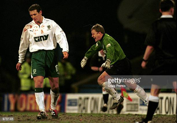Martin Taylor of Wycombe celebrates saving the final penalty as he runs past a dejected Mark Williams during the AXA sponsored FA Cup fifth round...