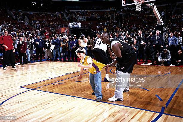 Michael Jordan of the Washington Wizards has some fun with a young fan during practice before the 2002 NBA All Star Game at the First Union Center in...