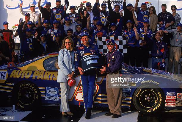 Michael Waltrip who drives the Chevy Monte Carlo for Dale Earnhardt Inc poses in the Victory Lane with his wife Buffy and the trophy after the...