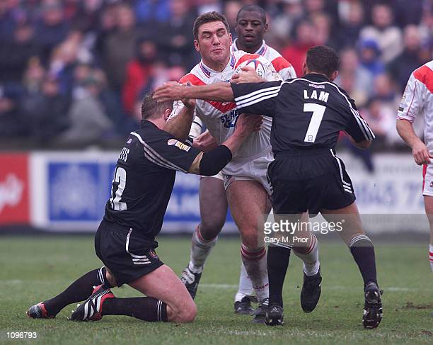 Sean Hoppe of St Helens is tackled by Adrian Lam and David Betts of Wigan during the Fourth Round of the Silk Cut Challenge Cup between St Helens v...