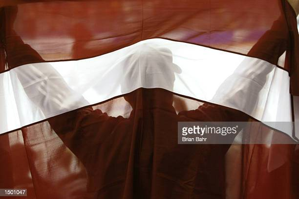 A Latvian fan holds up his country's flag in the preliminary round ice hockey game between Austria and Latvia during the Salt Lake City 2002 Winter...