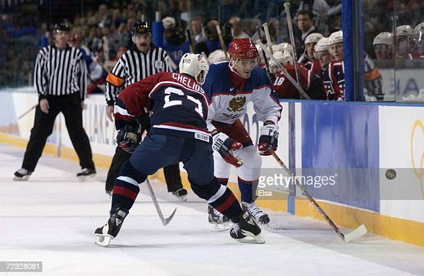 Alexei Yashin of Russia pokes the puck past defenseman Chris Chelios of the USA during the men's semifinals at the Salt Lake City Winter Olympic...