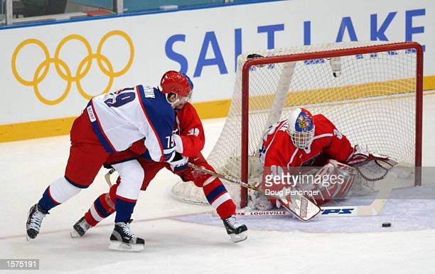 Alexi Yashin of Russia makes a wrap around shot under pressure from Jan Hrdina of the Czech Republic as Dominik Hasek makes a save in goal during...