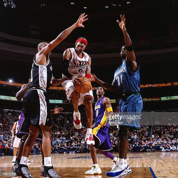 Allen Iverson of the Philadelphia 76ers drives to the basket against Tim Duncan of the San Antonio Spurs and Kevin Garnett of the Minnesota...