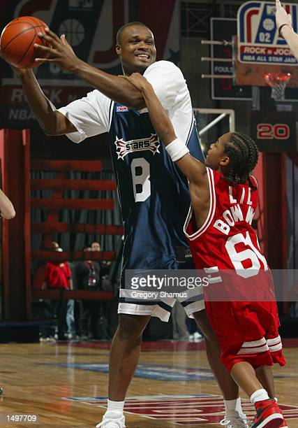 Antoine Walker of the Boston Celtics has fun with recording artist Lil Bow Wow during the MTV Rock and Jock Game at the NBA Jam Session Center Court...