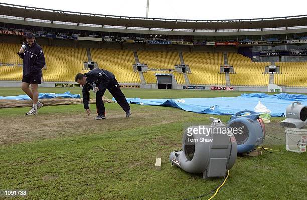 Ashley Giles and Graham Thorpe of England have a look at the wicket as the dries try to dry it after heavy rain during the England nets session at...