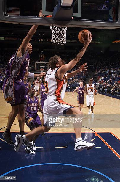 Bob Sura of the Golden State Warriors drives under Shawn Marion of the Phoenix Suns for the score at The Arena in Oakland California DIGITAL IMAGE...