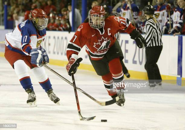 Cassie Campbell of Canada gets tripped up by Ekaterina Smolentseva of Russia in the third period of their preliminary round game during the Salt Lake...