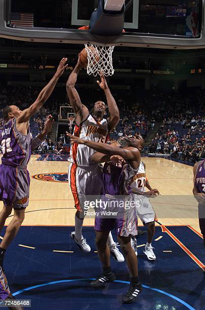 Center Erick Dampier of the Golden State Warriors shoots over forward Alton Ford of the Phoenix Suns during the NBA game at the Arena in Oakland in...