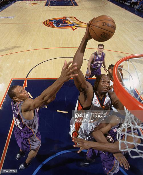 Center Erick Dampier of the Golden State Warriors shoots the ball as two Phoenix Suns forward Alton Ford and forward Shawn Marion attempt to block...